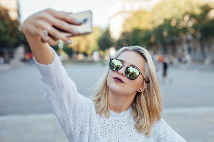 Young woman is taking a selfie by mobile phone.
